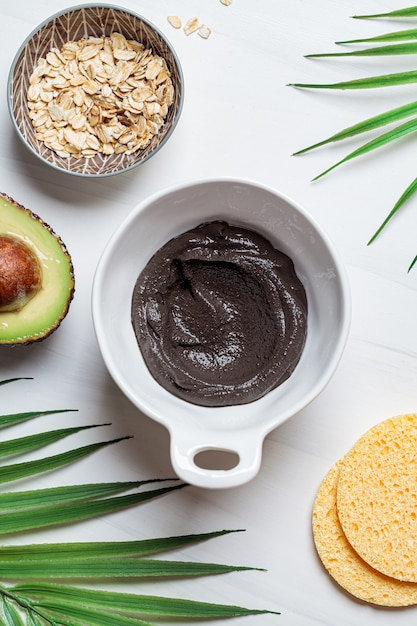 Maschera da cucina di argilla nera, avocado e farina d'avena, sfondo bianco. concetto di cura della pelle. pelle sana. Foto Premium