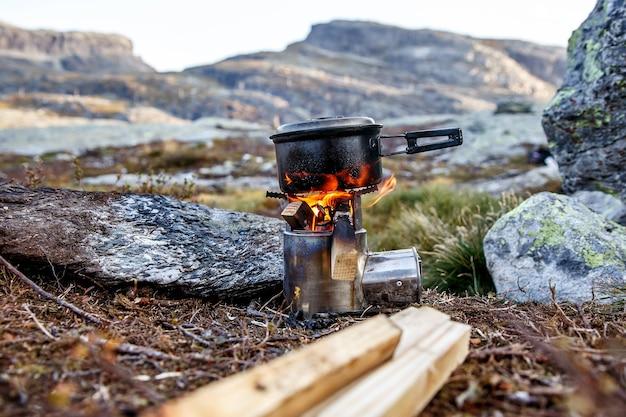 Cucinare su un piccolo fornello da campeggio in un campo di montagna. Foto Premium