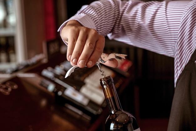 Tappare un costoso tappo di vino rosso in possesso di un giovane barista in piedi in un wine bar. Foto Premium