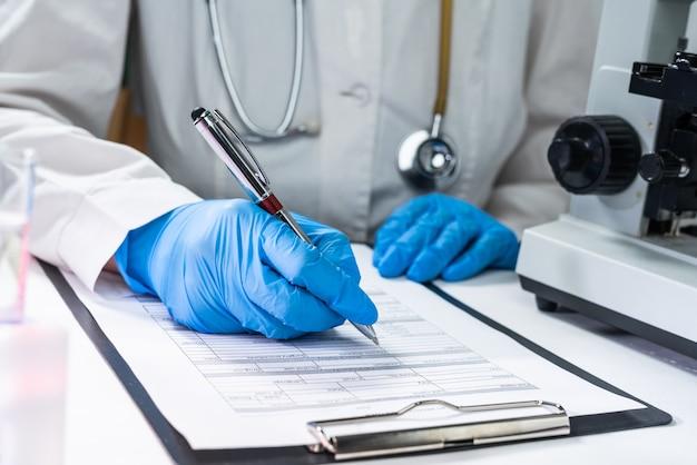 Coronavirus 2019-ncov virus, la mano del medico che tiene un campione di sangue e prende appunti scrivendo i dati dei pazienti su prescrizione medica Foto Premium