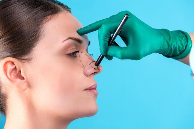 Chirurgo estetico che esamina cliente femminile in ufficio. il medico traccia le linee con un pennarello, la palpebra prima della chirurgia plastica, la blefaroplastica. mani del chirurgo o dell'estetista che toccano il fronte della donna. rinoplastica Foto Premium