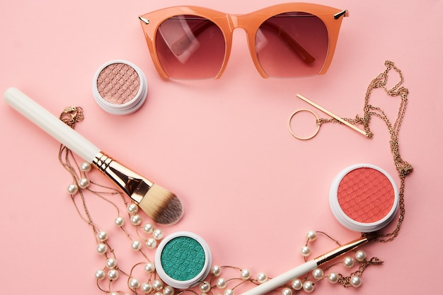 Cosmetici su sfondo rosa ombretto pennello polvere arrossire orologio Foto Premium