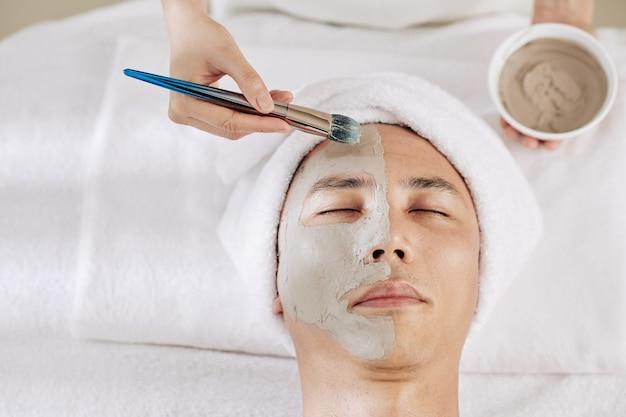 Cosmetologo che applica maschera all'argilla Foto Premium