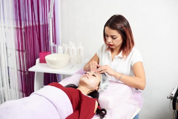 Cosmetologo che applica crema e massaggi donna Foto Premium
