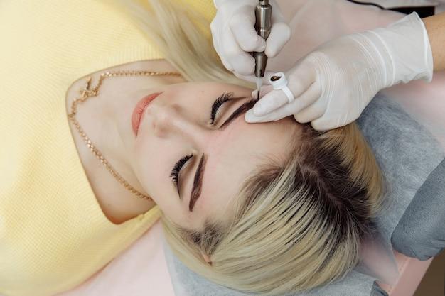 Cosmetologo in guanti bianchi che applica compongono con macchina per donna nel salone di bellezza Foto Premium