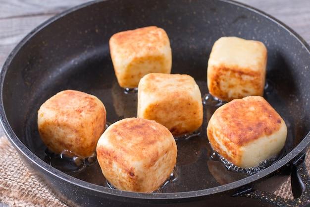 Frittelle di ricotta a forma di cubetti nella padella Foto Premium