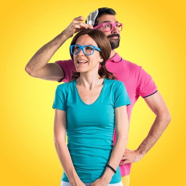 Coppia in abiti colorati tenendo una lampadina Foto Premium
