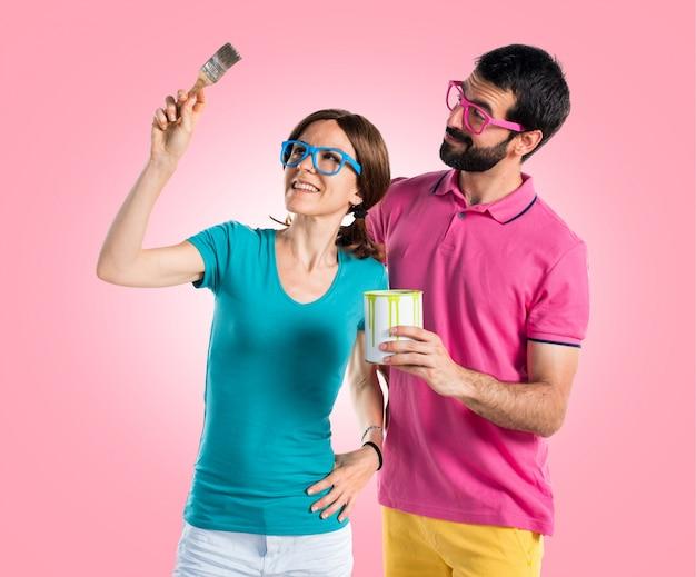 Coppia in abiti colorati in possesso di un vaso di vernice Foto Premium