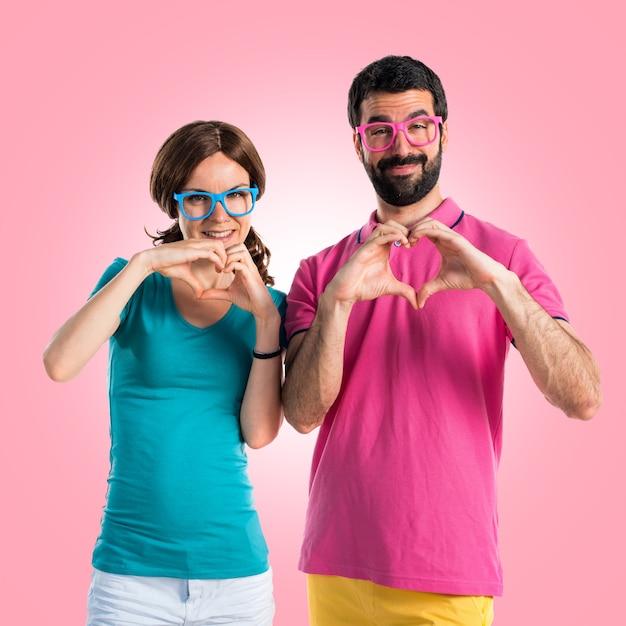 Coppia in abiti colorati facendo un cuore con le mani Foto Premium