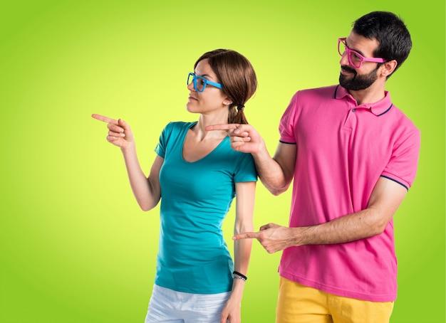 Coppia in abiti colorati che punta al laterale Foto Premium