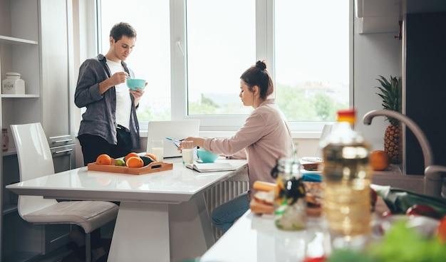 Coppia che mangia in cucina mentre si lavora online con un laptop e alcuni libri Foto Premium