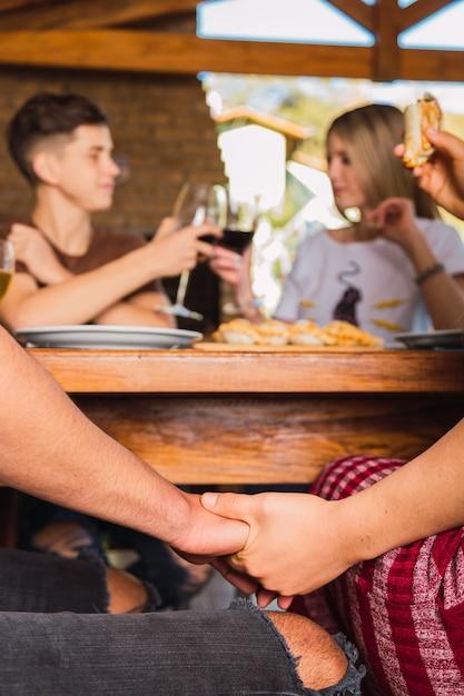 Coppie che tengono le mani mentre pranzano Foto Premium
