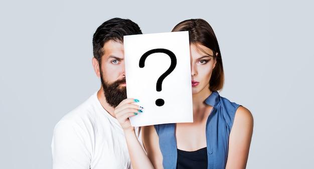Coppia in possesso di carta punto interrogativo. anonimo, domanda uomo e donna, incognita. Foto Premium