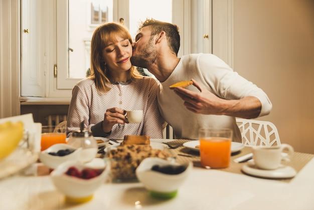 Coppia innamorata che fa colazione la mattina presto in cucina a casa e si diverte. Foto Premium