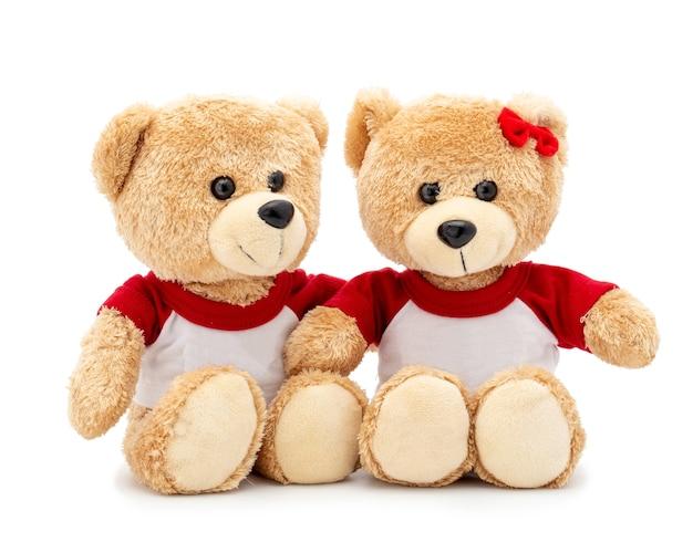 Coppia adorabile orsacchiotto marrone con maglietta e fiocco rosso isolato su uno spazio bianco Foto Premium