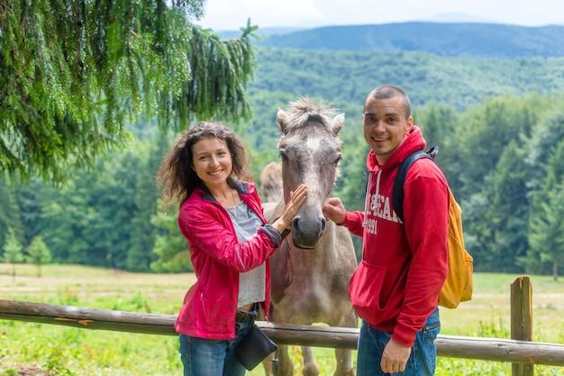 Coppia accarezzare il cavallo sul recinto di legno in terreni agricoli degli altopiani. Foto Premium