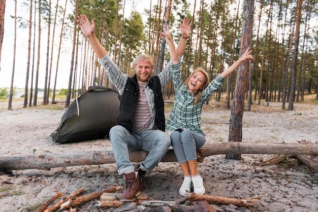 Coppia seduta su un albero caduto con le mani in aria Foto Premium