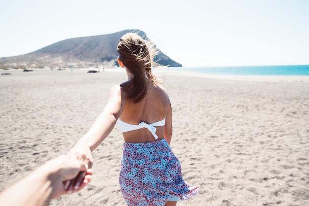 Coppia viaggio vacanze estive. donna che cammina tenendo la mano del marito che la segue, vista da dietro Foto Premium