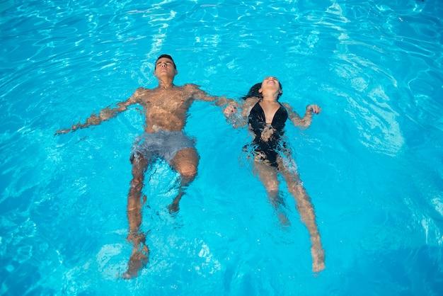 Coppia in piscina sull'acqua turchese in vacanza Foto Premium