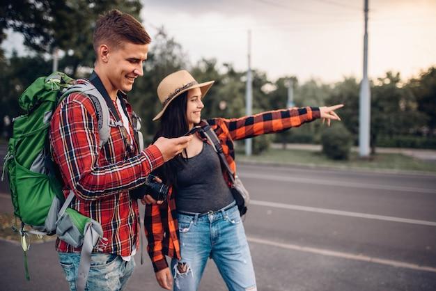 Coppia di turisti in cerca di attrazioni della città, escursione in città. escursioni estive. escursione all'avventura di un giovane uomo e una donna Foto Premium
