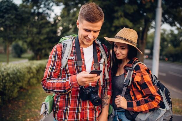 Coppia di turisti in cerca di attrazioni della città sul navigatore, escursione in città. escursioni estive. escursione all'avventura di un giovane uomo e una donna Foto Premium