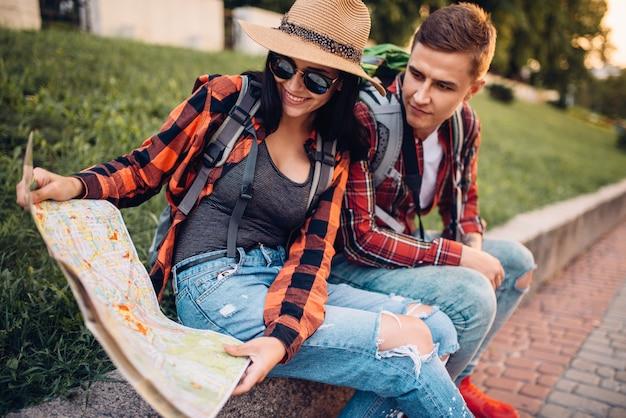 Coppia di turisti studia la mappa delle attrazioni, escursione in città. escursioni estive. escursione all'avventura di un giovane uomo e una donna Foto Premium
