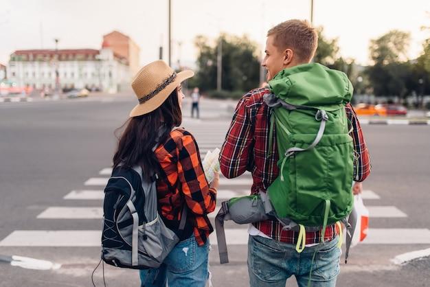 Coppia di turisti con zaini, vista posteriore, escursione in città. escursioni estive. escursione avventura di giovane uomo e donna, passeggiate in città Foto Premium