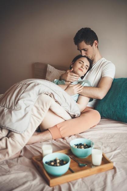 Coppia con sane abitudini sdraiato a letto pronto a mangiare cereali con latte Foto Premium