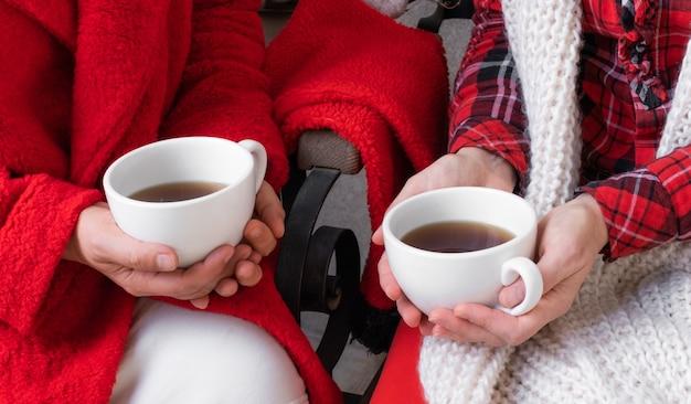 Coppia donna femmina azienda caffè tazza di tè rosso vestiti festivi natale capodanno san valentino Foto Premium
