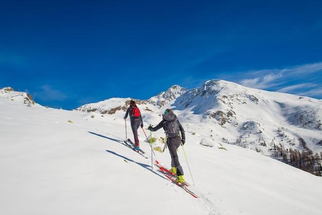 Un paio di donne praticano lo sci alpinismo Foto Premium