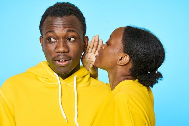 Coppia in felpe gialle, ragazza che bisbiglia all'orecchio del suo ragazzo Foto Premium