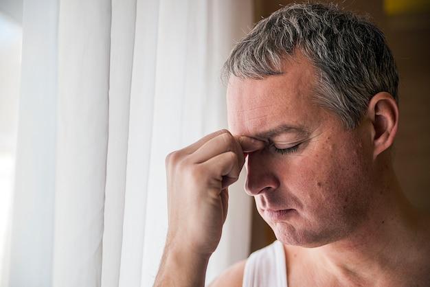 Valiente hombre de mediana edad mirando a la ventana, hombre de negocios triste y deprimido solo. hombre mirando a través de la ventana mirando preocupado, deprimido, pensativo y sufriendo sufrimiento solitario en la presión de trabajo o problemas personales concepto con espacio de copia Foto Premium