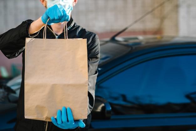 Corriere in maschera protettiva, guanti medicali forniscono cibo da asporto. pacchetto di cartone per dipendenti. posto per il testo. servizio di consegna in quarantena, 2019-ncov, pandemia coronavirus, covid-19. Foto Premium
