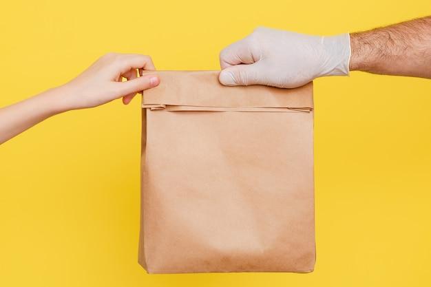 Un corriere in guanti medici di gomma passa un pacco di cibo. un volontario porta una scatola di cibo. Foto Premium