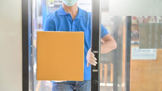 Il corriere che indossa una maschera e un guanto di gomma sta aprendo la porta dell'ufficio per consegnare i pacchi. Foto Premium