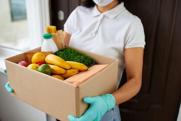 Corriere con scatola di imballaggio con cibo, consegna senza contatto, servizio di quarantena di coronavirus pandemico, donna volontaria con maschera protettiva bianca e scatola di donazione consegna guanti a casa. Foto Premium