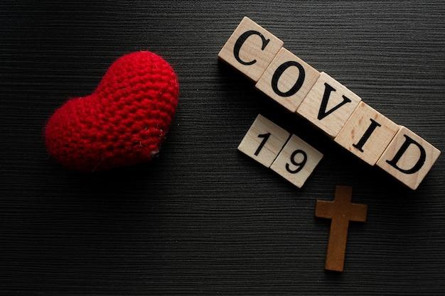 Covid-19 nome del virus corona dalla parola del testo di wuhan su fondo di legno di drak con amore del cuore. Foto Premium