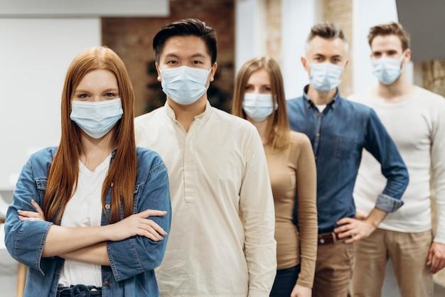 Colleghi che indossano maschere mediche al lavoro Foto Premium