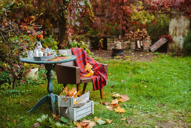 Accogliente patio. le foglie di autunno giacciono su un tavolo rotondo antico in legno con tazze di stoviglie, biscotti e candele. accanto a una vecchia sedia con tappeto colorato e casse di legno per terra. autunno cortile buio Foto Premium