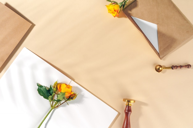 Busta di carta artigianale con rose gialle su sfondo beige Foto Premium
