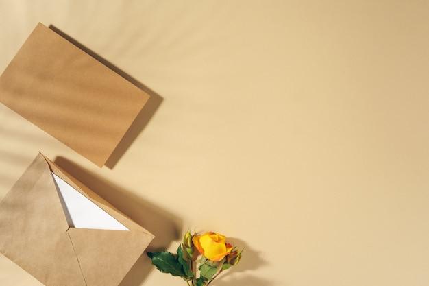Busta di carta artigianale con rose gialle sul tavolo beige Foto Premium