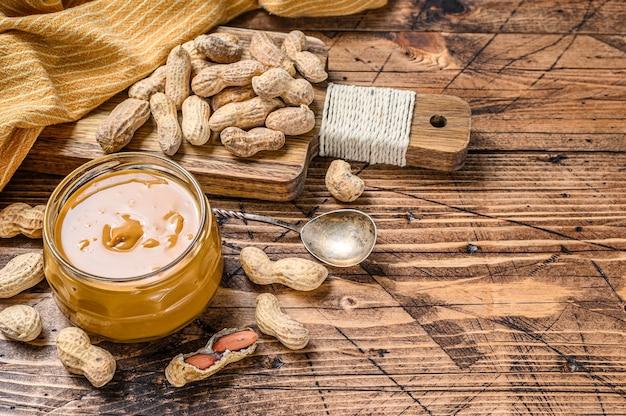 Burro di arachidi cremoso in vaso sulla tavola di legno Foto Premium