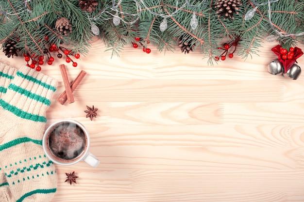 Cornice creativa fatta di rami di abete di natale su legno bianco con coni di decorazione rossa. Foto Premium