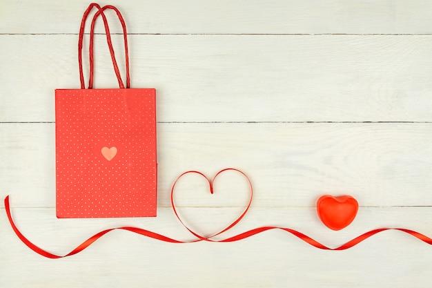 Composizione romantica creativa di san valentino con cuori rossi, nastro di raso e sacchetto di carta su fondo di legno. mockup con copia spazio per blog e social media. Foto Premium
