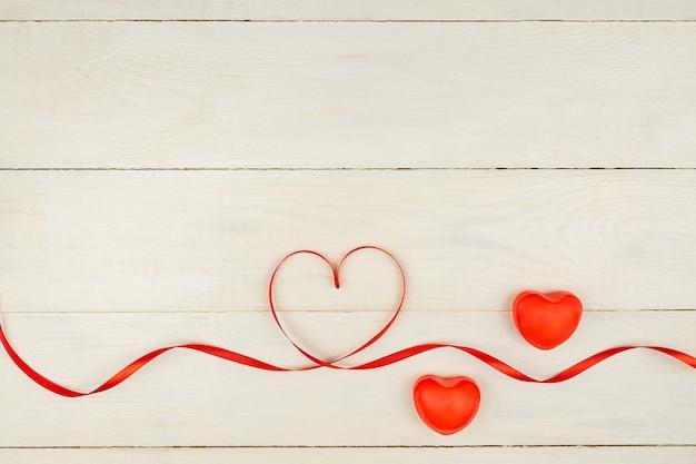 Composizione romantica creativa di san valentino con cuori rossi, nastro di raso su fondo di legno. mockup con copia spazio per blog e social media. Foto Premium