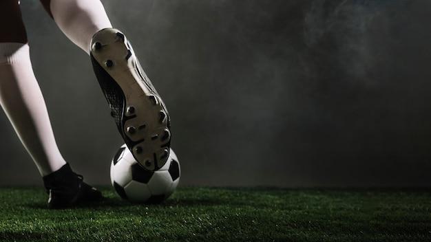 L'atleta del raccolto che dà dei calci al pallone da calcio Foto Premium