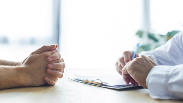 Ritaglia le mani di medico e paziente sulla scrivania Foto Premium
