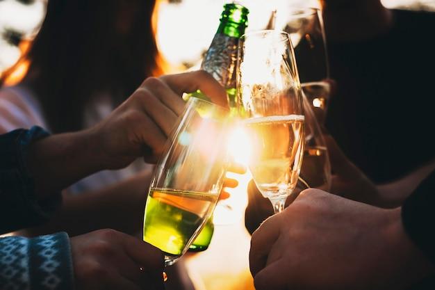 Ritaglia le mani dei giovani che tintinnano bicchieri e bottiglia di alcol contro il sole splendente mentre celebravano insieme le vacanze in campagna Foto Premium