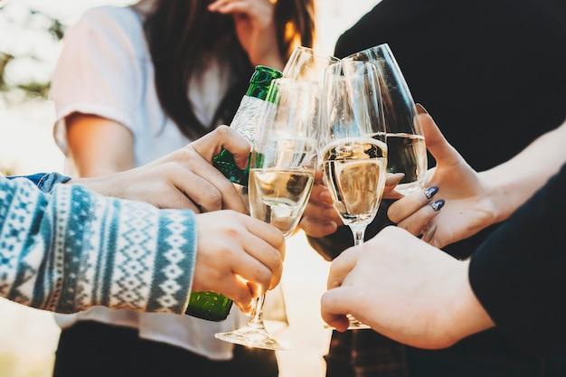 Ritaglia le persone che tintinnano bicchieri di champagne e bottiglia di birra mentre celebravano le vacanze in una giornata di sole nella natura Foto Premium