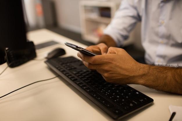 Immagine ritagliata dell'uomo d'affari utilizzando il telefono cellulare mentre è seduto alla scrivania Foto Premium